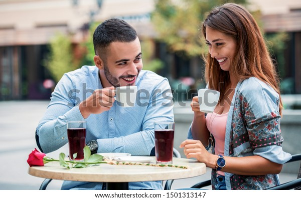 Flirting in a cafe. Beautiful loving couple sitting in a cafe drinking coffee and enjoying in conversation. Love, romance, dating