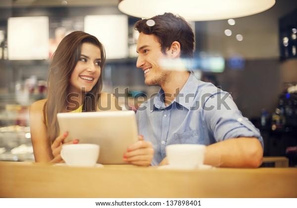 カフェでカップルをちらつかせるデジタルタブレット