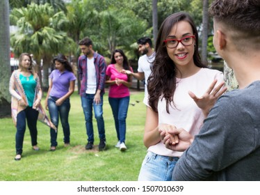 Flirting couple with group of friends outdoor in summer in city