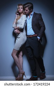 flirting fashion couple standing embraced in studio