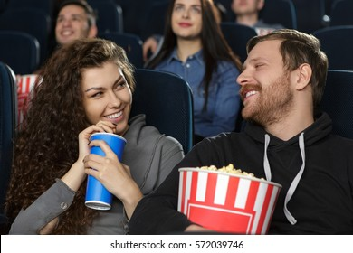 Flirting with her man. Gorgeous woman sipping her coke looking seductively on her boyfriend while at the cinema together loving couple flirting at the movie theatre looking at each other love concept