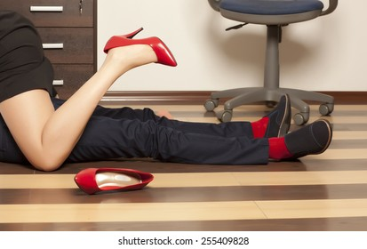 Flirting. Low section of business couple getting intimate on floor in office