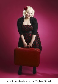 Flirting pin-up girl and old retro suitcase and she looks toward the camera, pink background