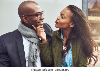 Flirting young African American woman pursing her lips for a kiss and caressing the face of a handsome man in glasses as they enjoy a date together