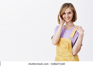 Flirty attractive fair-haired european female coworker in yellow dungarees over purple t-shirt, playing with hair strand and gazing with sensual smile at camera, posing and seducing someone hot