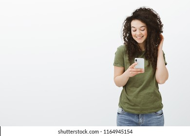 Flirty beautiful curly-haired girl in dark-green t-shirt, touching curls and smiling broadly at smartphone screen while watching funny video on device or messaging with boyfriend over gray wall