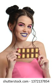 Flirty beautiful woman eating bar of chocolate and looking at camera. Studio shot.