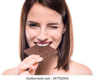 Flirty beautiful woman eating bar of chocolate and looking at camera. Studio shot.