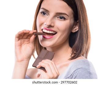Flirty beautiful woman eating bar of chocolate and looking away. Studio shot.