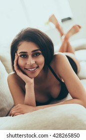 Flirty beauty. Beautiful young mixed race woman in black lingerie looking at camera and smiling while lying on couch at home