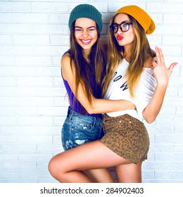 Flirty beauty. Portrait of beautiful young  two attractive young women making selfies together. Dressed in shorts and a bright cap on a white background.