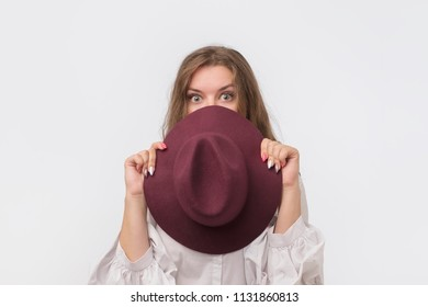 Flirty funky caucasian woman hiding behind fashionable trendy red head wear, with wide open eyes.