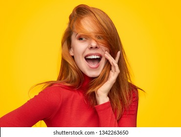 Flirty happy redhead girl posing with bright smile on orange background