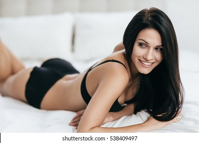 Flirty look. Irresistible young woman in black underwear looking away while lying on the bed at home