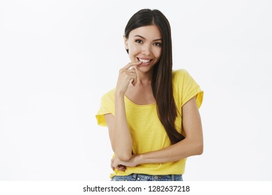 Flirty and sexy good-looking tanned female with long dark hair in yellow t-shirt without makeup smiling sensually and curious biting finger looking intrigued and seducing at camera over white wall