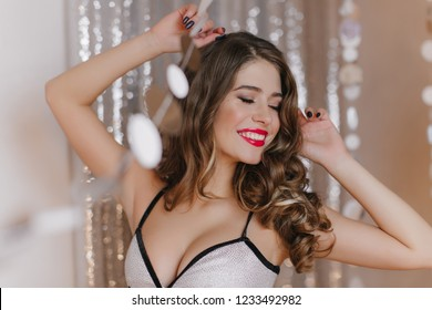 Flirty stylish lady confusedly closed her eyes. Girl in fashionable elegant top posing on background of gray garlands