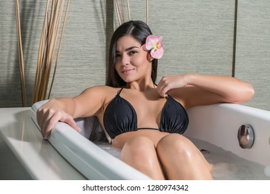 Flirty young brunette in black bikini lying in healing bath in massage center smiling at camera