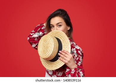 Flirty young female in stylish floral clothes covering face with straw hat and looking at camera against vivid red background