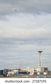 A float plane flies over the Seattle waterfront with the Space Needle shown.