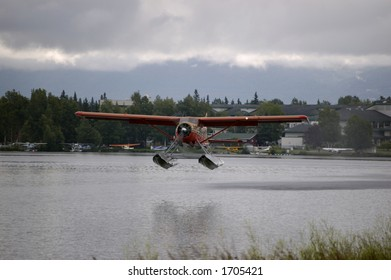 A float plane takes off from a lake in Anchorage Alaska