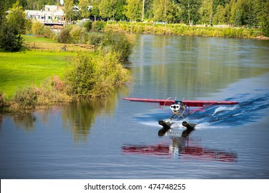 Float plane taking off from Chena River in Fairbanks, Alaska on a bright summer day