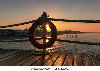 A floatation ring on wooden pier in Side on sunrise