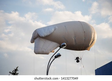 floating in the air among the clouds white airship, aircraft for advertising goods and services and high-altitude photo and video flying in the sky over the city at a low altitude