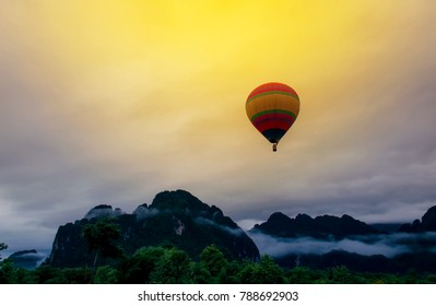 Floating balloon with misty in the morning,Balloon floating over misty mountain on morning at Vang Vieng, Laos.