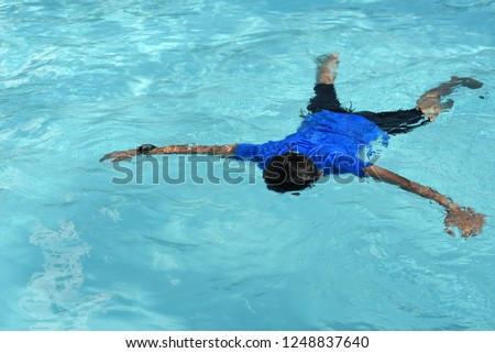 9152c82b214 floating body of a drowned male children in swimming pool. concept of safety