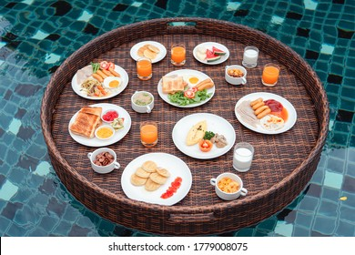 floating breakfast , Breakfast tray with food and orange juice in swimming pool. Summer concept