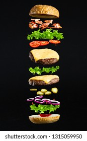 Floating burger isolated on black background. Ingredients of a delicious burger with ground beef patty, lettuce, bacon, onions, tomatoes and cucumbers