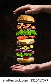Floating burger isolated on black wooden background in men hands. Ingredients of a delicious burger with ground beef patty, lettuce, bacon, onions, tomatoes and cucumbers