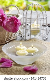 Floating candles in water, aromatic petals in the background