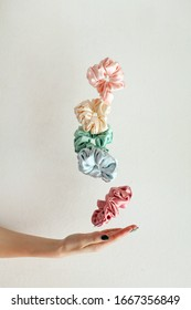 Lot of floating Colorful silk Scrunchies on womas hand isolated white. Hairdressing tools and accessories. Hair Scrunchies, Elastic HairBands, flying or falling Scrunchie Hairband for girl. copy space