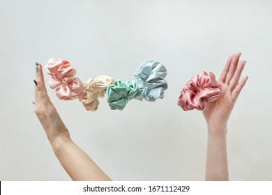 Lot of floating Colorful silk Scrunchies on womas hands isolated white. Hairdressing tools and accessories. Hair Scrunchies, Elastic HairBands, flying or falling Scrunchie Hairband for girl. copy