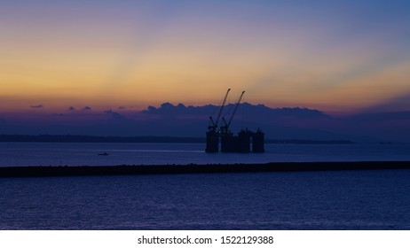 floating crane platform in the rays of the setting sun. beautiful golden sunset. industrial cranes in the ocean on a multi-colored sky background. ecology and industry problem