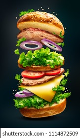 Floating delicious burger with flying ingredients isolated on dark background with clipping path