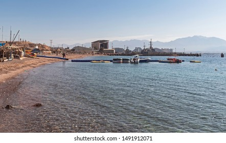 a floating dock and small boats at the sailing and sea sport club near the naval facility and harbor in eilat in israel with hotels in the far background