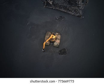 Floating Excavator digging in shoreline of serangan bay, bali. Amphibious Tracktor