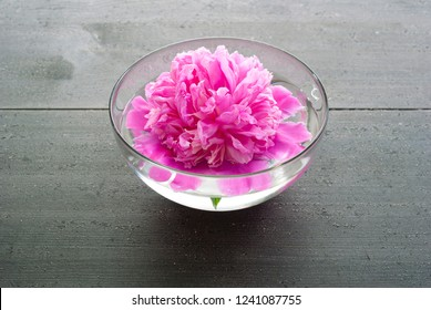floating flower at aroma bowl on black wooden table