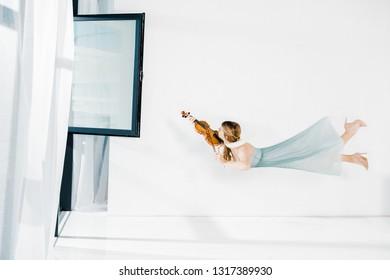 floating girl in blue dress playing violin near window