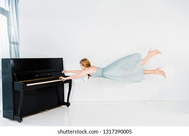 floating girl in blue dress playing black piano on white background