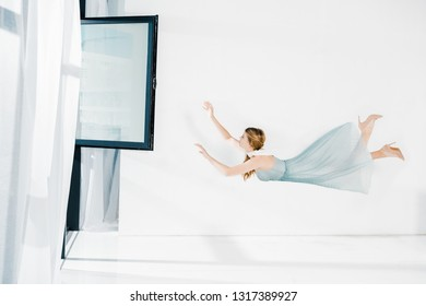floating girl in blue dress raised hands near window with copy space