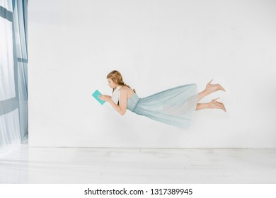 floating girl in blue dress reading book in air with copy space