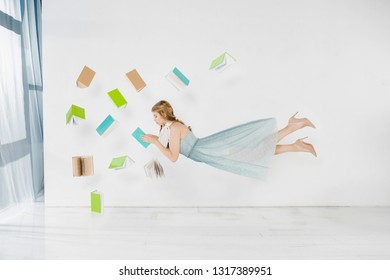 floating girl in blue dress reading book in air on white background