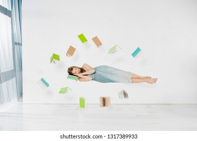 floating girl in blue dress sleeping on book in air on white background