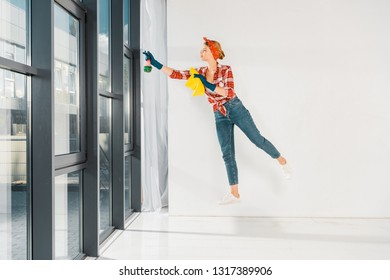 floating girl in jeans and plaid shirt cleaning windows with rag and spray