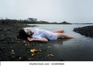 Floating girl lying on the rock of dark river
