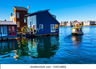 Floating Home Village Blue Houseboats Water Taxi Fisherman's Wharf Reflection Inner Harbor, Victoria British Columbia Canada Pacific Northwest.  Area has floating homes, piers, restaurants.