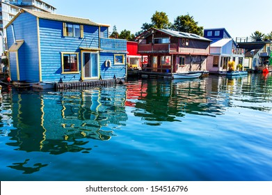 Floating Home Village Blue Red Brown Houseboats Fisherman's Wharf Reflection Inner Harbor, Victoria British Columbia Canada Pacific Northwest.  Area has floating homes, boats, piers, and restaurants.